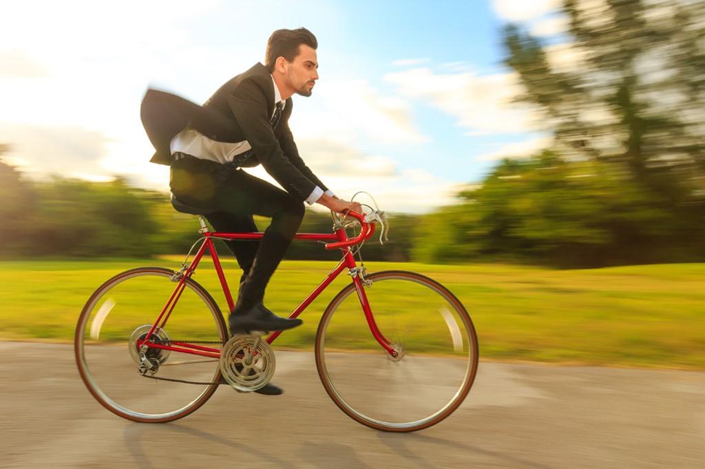 Fahrender Radfahrer im Anzug